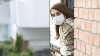 Woman wearing a mask looks out a window at the camera